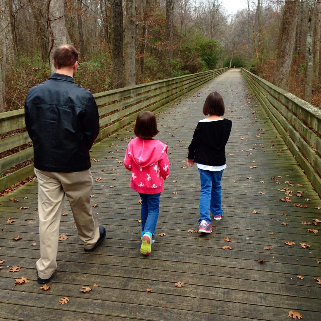 Image is of a man and two young girls taking a family walk down a long wooden bridge leading onto a gravel walking trail in a wooded area.